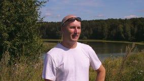 Gladlynt vuxen man som ser på grön skog med sjön och tycker om sommardag lager videofilmer