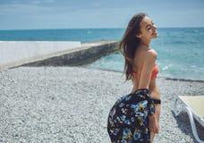 Gladlynt yong kvinna på bakgrund av havet Arkivbild