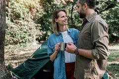Gladlynta älska par som dricker den varma drycken i skog Arkivfoto