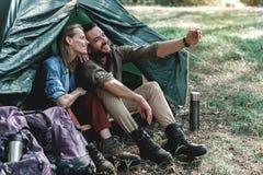 Gladlynta älska par som tar fotoet av dem i skog royaltyfria bilder