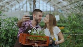 Gladlynta älska parträdgårdsmästare som tar selfiebilden på smartphonekamera och kysser, medan arbeta i växthus lager videofilmer