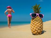Gladlynta ananasexponeringsglas och en kvinna i en bikini som solbadar på stranden på havsbackgrounde, sätter på land på havsbakgr Royaltyfri Foto