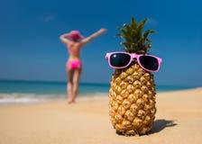 Gladlynta ananasexponeringsglas och en kvinna i en bikini som solbadar på stranden på havsbackgrounde, sätter på land på havsbakgr Fotografering för Bildbyråer