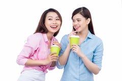 Gladlynta asiatiska kvinnliga vänner som rymmer kaffe, rånar att tycka om en konversation Royaltyfri Foto