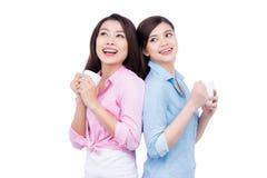 Gladlynta asiatiska kvinnliga vänner som rymmer kaffe, rånar att tycka om en konversation fotografering för bildbyråer