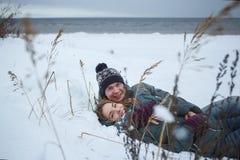 Gladlynta barnpar som ligger i snö nära se-stranden Romanctic ferie för vinter Arkivbilder