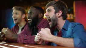 Gladlynta blandras- vänner som firar lagsegern som ger nävebulan, lopp stock video