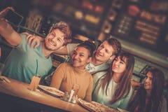 Gladlynta blandras- vänner som har gyckel som äter i pizzeria royaltyfri foto