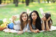 Gladlynta Caucasian och asiatiska flickor som tar selfie på smartphonen Arkivfoto