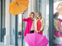 Gladlynta damer som poserar med paraplyerna Royaltyfri Foto