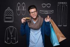 Gladlynta den shoppingpåsar och visningen för ung man hållande avfärdar kortet royaltyfria bilder