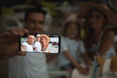 Gladlynta föräldrar som fotograferar med barnet på mobil Arkivbild