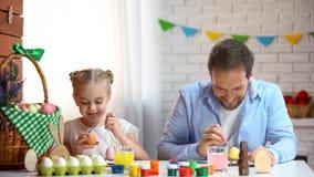 Gladlynta fader- och dotterfärgläggningägg som tillsammans spenderar tid, kreativitet royaltyfria bilder