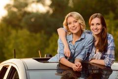 Gladlynta flickor som sitter i bilen Royaltyfri Foto