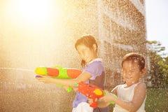 Gladlynta flickor som spelar vattenvapen i parkera Arkivfoton