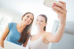 Gladlynta flickor som tar selfies Arkivbild