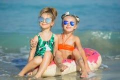 Gladlynta flickvänner svävar på en cirkel på havet arkivfoton