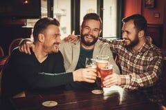 Gladlynta gamla vänner som har roligt och dricker utkastöl i bar Arkivbild