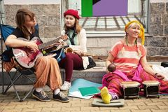 3 gladlynta gatamusiker som spelar musik på en trottoar arkivbilder