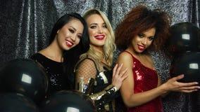 Gladlynta glamourkvinnor med svarta ballonger lager videofilmer
