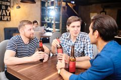 Gladlynta grabbar som dricker öl i bar royaltyfri fotografi