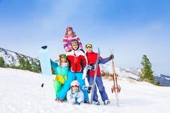Gladlynta grabbar som står med snowboards och, skidar royaltyfri foto