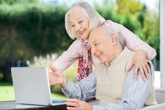 Gladlynta höga par genom att använda bärbara datorn royaltyfri foto