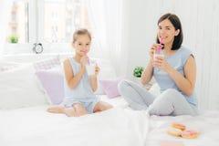 Gladlynta iklädda pyjamas för moder och för dotter, har frukosten i morgonen, drinkmilkshake med munkar, sitter korsade ben på c royaltyfri fotografi