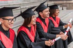 Gladlynta kandidater som kopplar av på trappuppgång med diplom i händer Fotografering för Bildbyråer