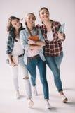 Gladlynta kvinnastudenter som går med läroböcker i händer Fotografering för Bildbyråer