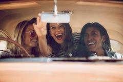 Gladlynta kvinnliga vänner som går på en vägtur royaltyfri foto