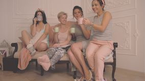 Gladlynta kvinnliga vänner som gör pajamapartiet arkivfilmer