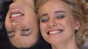 Gladlynta kvinnliga vänner som skrattar det liggande huvudet - till - huvud, sunt leende, toothcare arkivfilmer