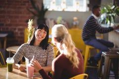 Gladlynta kvinnliga vänner som talar, medan sitta med nya drinkar på tabellen royaltyfria foton