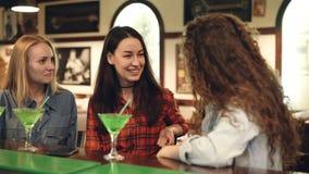 Gladlynta kvinnliga vänner umgås i utsmyckad stång Attraktiva kvinnor är prata, skratta och trycka på coctailen arkivfilmer