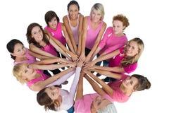 Gladlynta kvinnor sammanfogade, i en cirkel och att se upp på camerawearinen Royaltyfri Foto