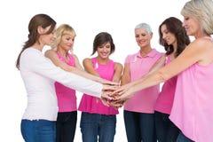 Gladlynta kvinnor som poserar i bärande rosa färger för cirkel för bröstcancer Fotografering för Bildbyråer
