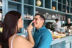 Gladlynta älska par som har gyckel i kafeteria Arkivbild