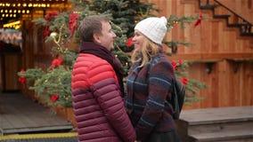Gladlynta lyckliga barnpar som har roligt och kysser på julmarknaden Mannen och kvinnan spenderar Tid tillsammans på stock video