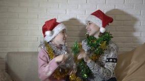 Gladlynta lyckliga små flickor i röda hattar av Santa Claus spelar med de glitter, skrattet och leendet som sitter på stock video