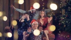Gladlynta lyckliga vänner som firar nytt år för jul, festar att se in i kamera stock video