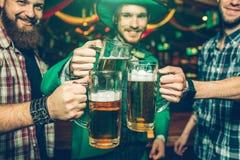 Gladlynta lyckliga vänner står tillsammans i bar och jubel De rymmer rånar av öl nästan Folkleende dem royaltyfri bild