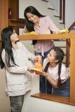 Gladlynta mång--generationsbundna kvinnor som gör det rena huset royaltyfri bild