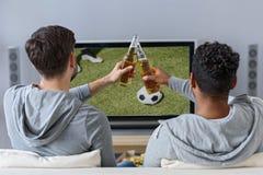 Gladlynta manliga vänner som underhåller med tv fotografering för bildbyråer