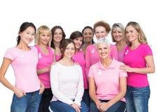 Gladlynta nätta kvinnor som poserar och bär rosa färger för bröstcancer Arkivfoton