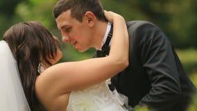 Gladlynta nygifta personer som omfamnar, i grön sommar, parkerar Den stiliga brudgummen vippar på och kysser försiktigt hans älsk lager videofilmer