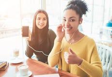 Gladlynta och attraktiva flickor sitter nära det ljusa fönstret i kafé En flicka som lyssnar till musik medan annan arkivbilder