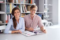 Gladlynta par av teknikerer som har rolig läsning en bok i en arkitektstudio Royaltyfri Bild