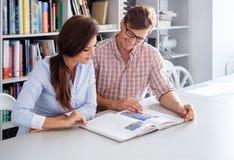 Gladlynta par av teknikerer som har rolig läsning en bok i en arkitektstudio Arkivbilder