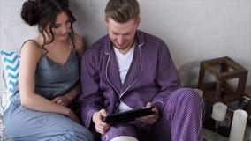 Gladlynta par genom att använda deras minnestavla för att köpa direktanslutet hemma i sovrum arkivfilmer